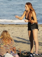 Lindsay Lohan showing off her seductive body wearing black bikini top and shorts at the beach in Malibu from CelebMatrix