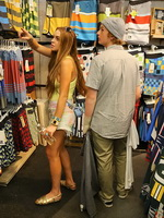 Lindsay Lohan braless in tiny yellow top and painted denim shorts at Jack's Surf Shop in Huntington Beach from CelebMatrix