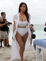 Kim Kardashian showing off her hourglass curves in white monokini at the beach in Miami from CelebMatrix