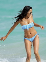 Padma Lakshmi busty wearing light-blue tube bikini on the beach in Miami from CelebMatrix