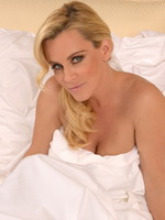 Jenny McCarthy naked but covered in bed for a Christmas photoshoot from CelebMatrix