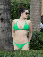 Kelly Brook shows off her curvy body wearing skimpy green bikini poolside in Miami from CelebMatrix