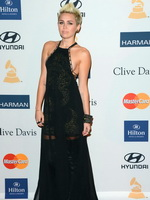 Miley Cyrus showing side boob in a black partially see-thru dress at Clive Davis pre Grammy gala in Los Angeles from CelebMatrix