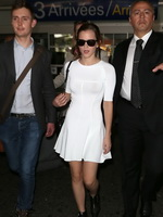 Emma Watson braless wearing white tight mini dress at the airport in France from CelebMatrix