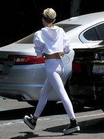 Miley Cyrus booty in white tights and belly top trying to hide from paparazzi out of studio in LA from CelebMatrix