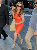 Alyssa Milano braless wearing tight orange mini dress outside the studio in New York City from CelebMatrix
