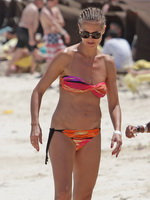Heidi Klum showing off her hot body in a tube colorful bikini at the beach in the Bahamas from CelebMatrix