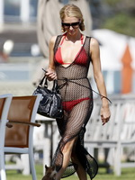 Paris Hilton wearing tiny red bikini and fishnet dress at the beach in Malibu from CelebMatrix