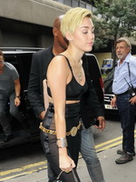 Miley Cyrus pantyless wearing black see-through pants and belly top outside her hotel in London from CelebMatrix