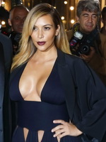 Kim Kardashian braless showing huge cleavage in a low cut black dress at the Mademoiselle C premiere in Paris from CelebMatrix