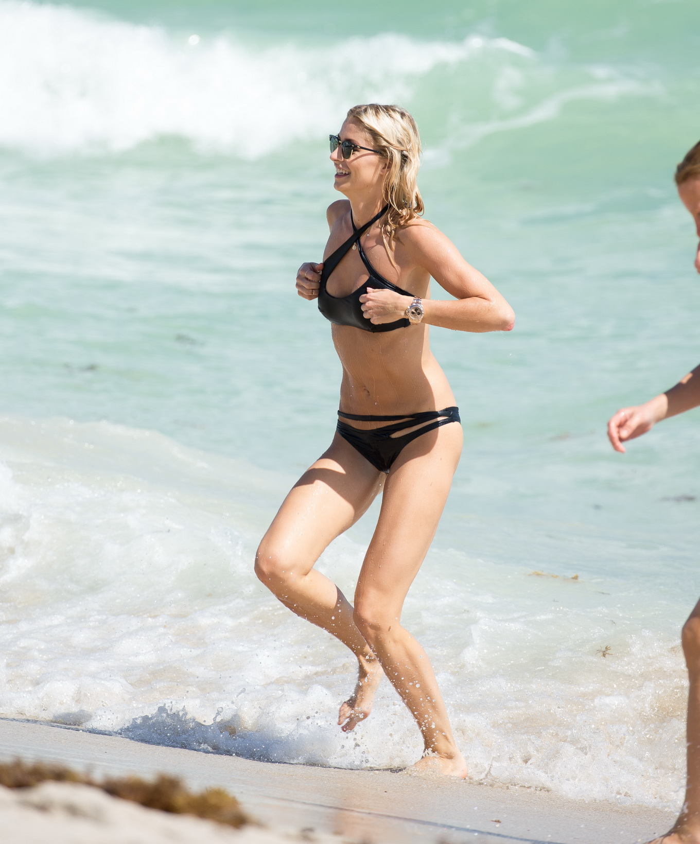 showing off her hot body in skimpy black bikini at the beach in miami