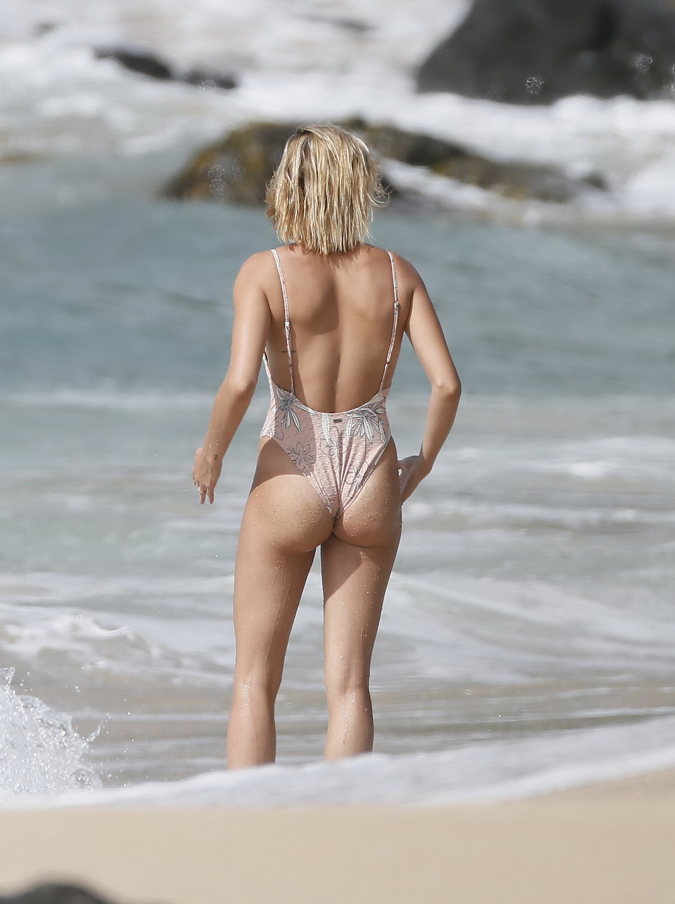 Hailey Baldwin in a floral nude swimsuit washing her sandy ...