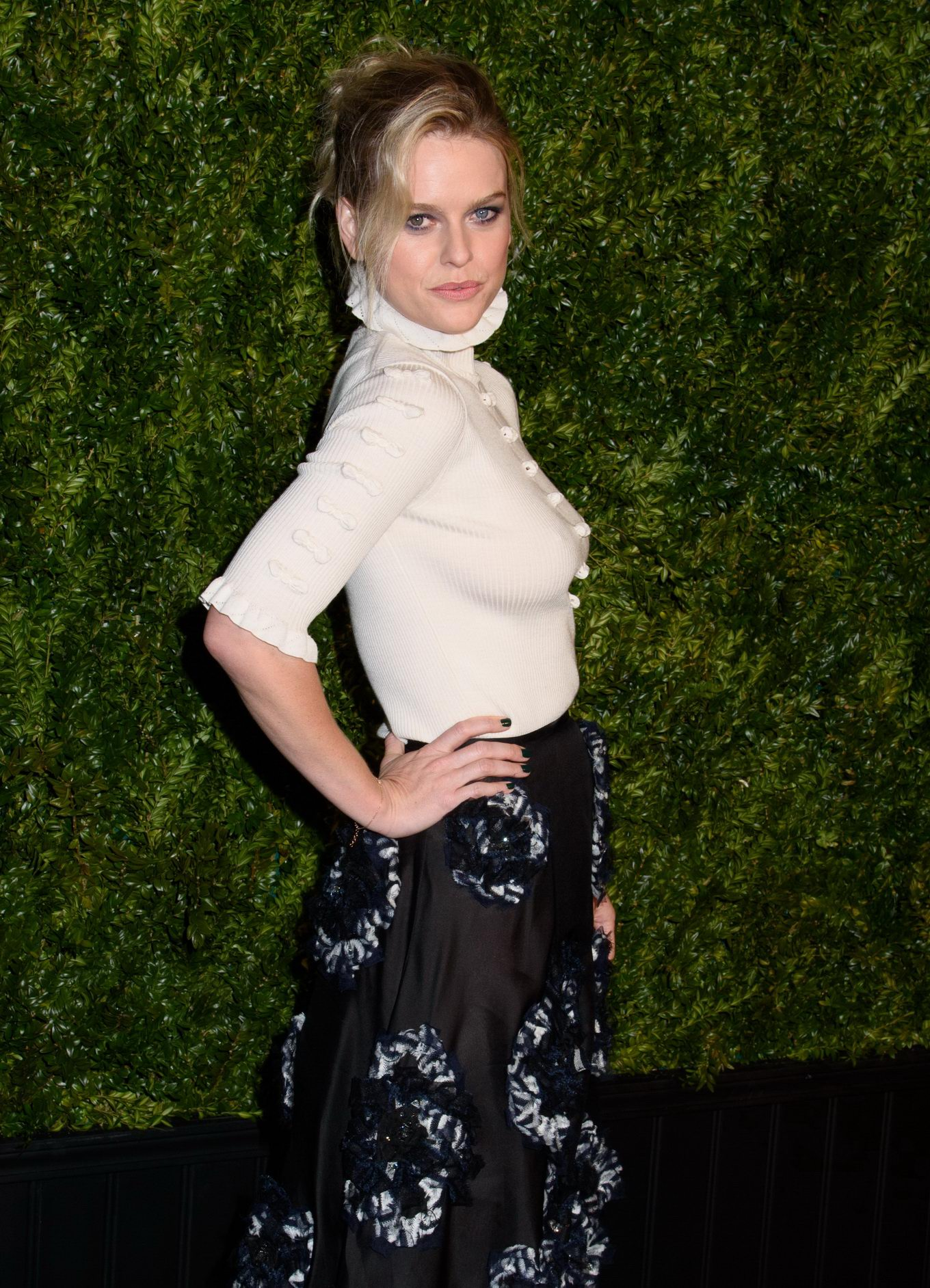 Alice Eve braless in white turtleneck top and black skirt ...